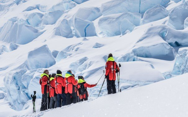 People in red expedition jackets hiking up an iceberg.