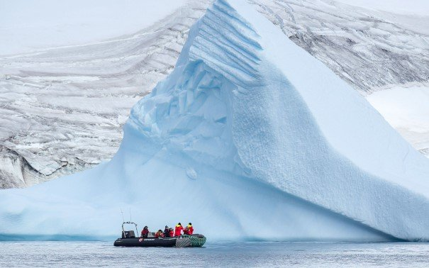Small expedition boat in front of an Iceberg.