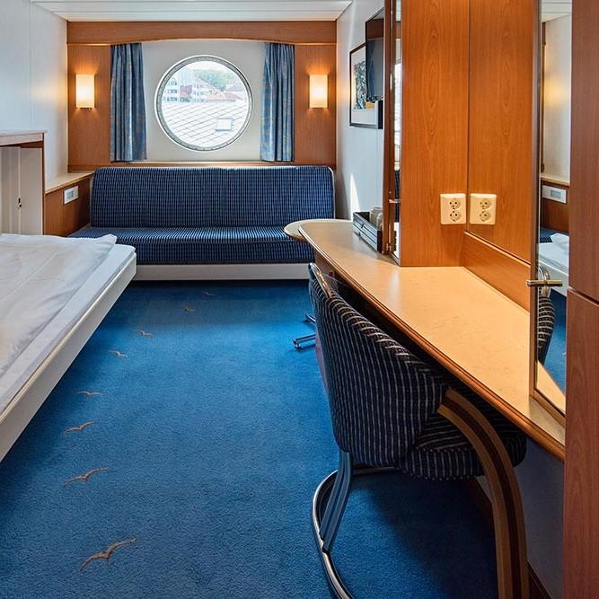 Ein Schlafzimmer mit einem Bett und Schreibtisch in einem kleinen Zimmer
